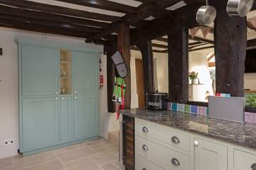 Bespoke fitted cupboards house the microwave as well as plenty of storage space.