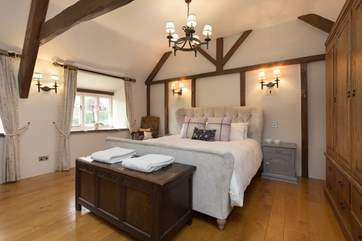 This is the master bedroom. A stunning high room with solid wood floors, high ceilings with beams and a brand new en suite shower-room.