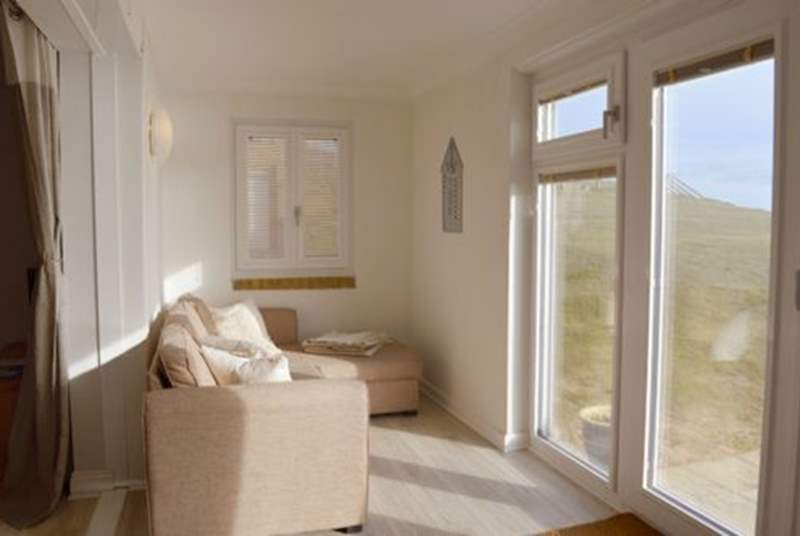 Sit and enjoy the picturesque scene  of Freshwater Bay from the lovely sun-room.