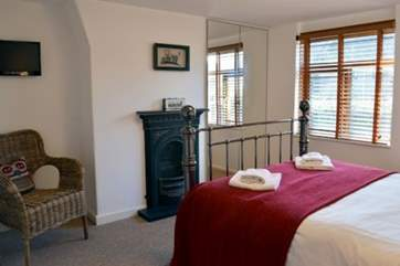The second double bedroom has a TV for lazy mornings and original Victorian feature fireplace