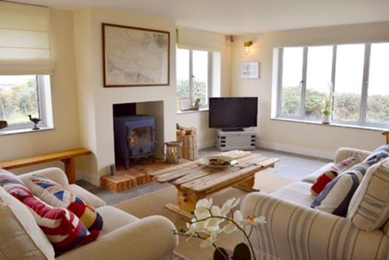 The cosy sitting-room is a delightful space to relax and enjoy the views, TV or a favourite film