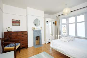 The master bedroom is complete with a  tiled 1930s ornamental fireplace