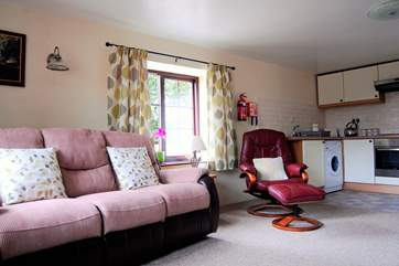 The open plan living-room is very comfortable with a reclining sofa and easy chair.