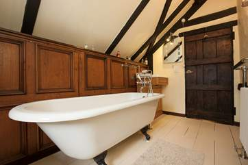 The family bathroom with oak paneling and claw-foot, roll-top bath.