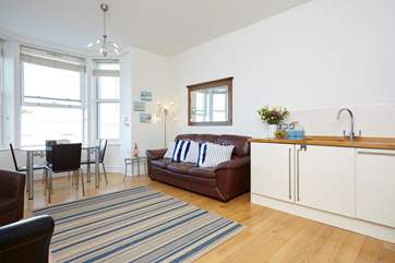 The open-plan space has high ceilings, wooden floor and large bay window with extensive sea view!