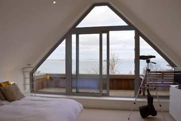 The master bedroom with doors opening out to the Juliet balcony with seating to enjoy the fabulous view
