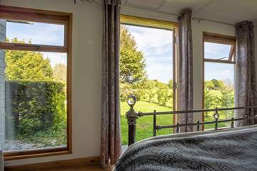 A bed with a view and double doors leading out to the garden area.