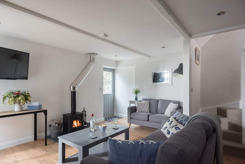 The open plan living-room with sofas around the wood-burner is perfect for relaxing with friends or family.