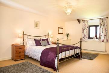 Wonderfully spacious bedroom 1 has a king-size double bed, a gorgeous bedstead and a handy vanity unit.