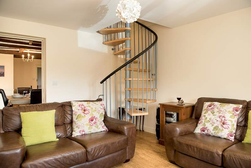 The second sitting-room/snug is an ideal space for those who might like some quiet time. The spiral stairs lead up to bedroom 4 on the mezzanine floor above.