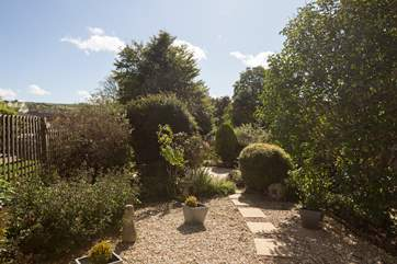 The garden has pretty planting around the gravelled areas and a patio with views down the valley.