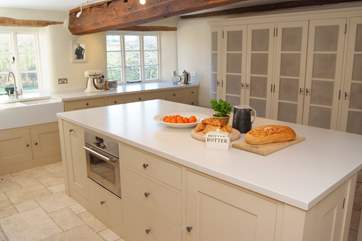 The kitchen features this huge island with storage to one side and the breakfast-bar to the other.