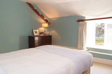 This bedroom looks out to the sheltered courtyard area and gardens at the  back of the farmhouse.
