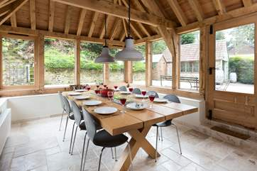This light filled oak framed dining room seats all 12  guests easily. There is direct access outside too.
