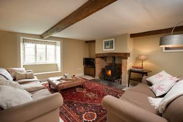 This is the living room with a wood burning stove, deep comfortable sofas and a lovely warm atmosphere.