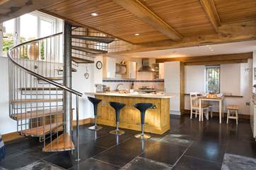 The spiral staircase provides a divide between the kitchen/dining areas and the sitting-area.