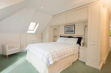 The light master bedroom has plenty of space, and also has a door out to the balcony
