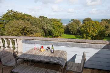 Enjoy a drink of the terrace with views through the trees to the sea