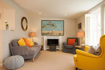 A cosy yet spacious sitting-room with vibrant colours bringing light and character to the room.