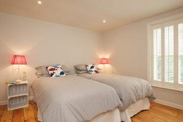 The beautifully decorated and spacious twin bedroom has views over the front garden.