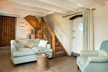 The cosy sitting-room with the stairs leading up to bedroom 2 and the family bathroom.
