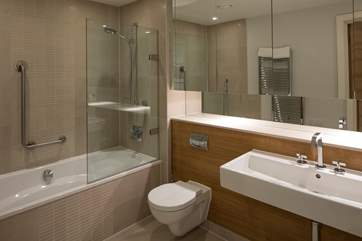 The main bathroom offers a bath, shower and the most gigantic mirror with endless storage space for all your personal toiletries.