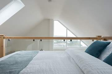 Glass balustrading allows the view to be seen from the bed.