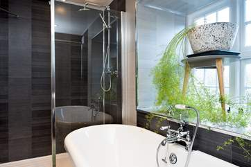 The bathroom not only has a beautiful roll-top  bath but also has a large drench-head shower.