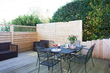 Sheltered decked area with outdoor sofas to sit back and relax after a hard day at the beach.