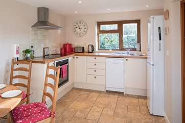 The modern kitchen has an induction hob, dishwasher and large fridge/freezer.