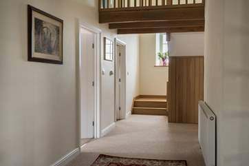 The entrance hallway with the twin bedroom and kitchen to the left, and sitting and dining rooms to the right, or head straight upstairs to the bedrooms.