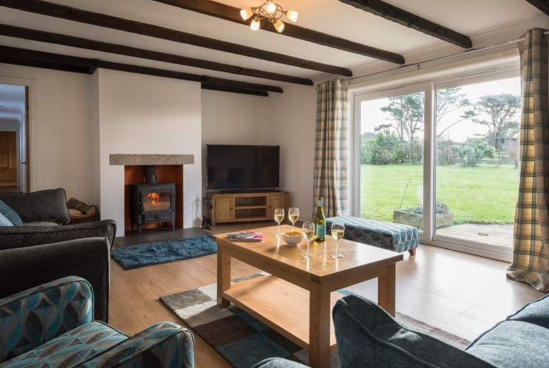 The main sitting-room has a wood-burner and doors out to the garden.