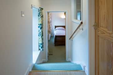 Four steep steps lead down to bedroom 2, the utility-room is to the right of the photograph.