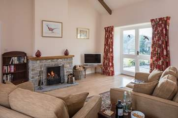 The sitting room has a cosy open fire and French doors that lead out onto the beautiful garden.