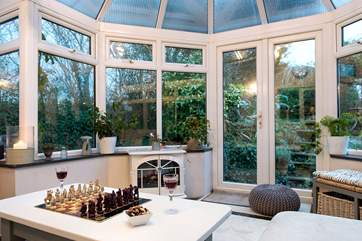 The conservatory is at the back of the cottage overlooking the garden - it has a wood-burning effect electric stove making it super cosy on chiller evenings.