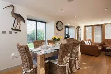 The dining-table is set to one side of the room which has plenty of light and space.