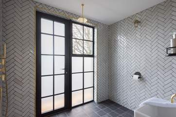 The wet-room has floor to ceiling herringbone tiles and a glass shower screen.