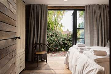 Doors open from the bedrooms and living space onto the garden and hot tub deck.