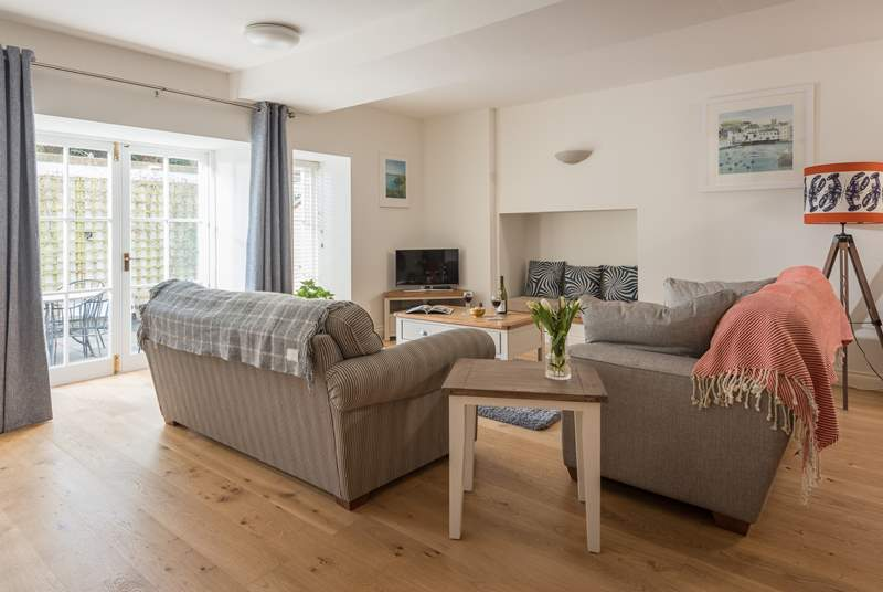 The spacious open plan living-room has two big sofas for stretching out on.