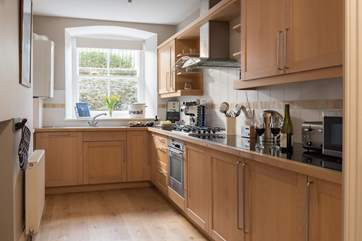 Solid wood kitchen units and granite tiled work surfaces show the quality of the kitchen.