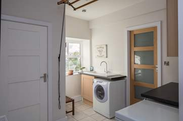 The spacious utility-room is neatly connected to the kitchen. Perfect for storage or a spot of food preparation.