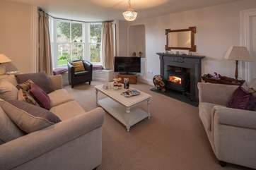 The sitting-room is cosy yet spacious, with stunning views across over the garden and out over the water.