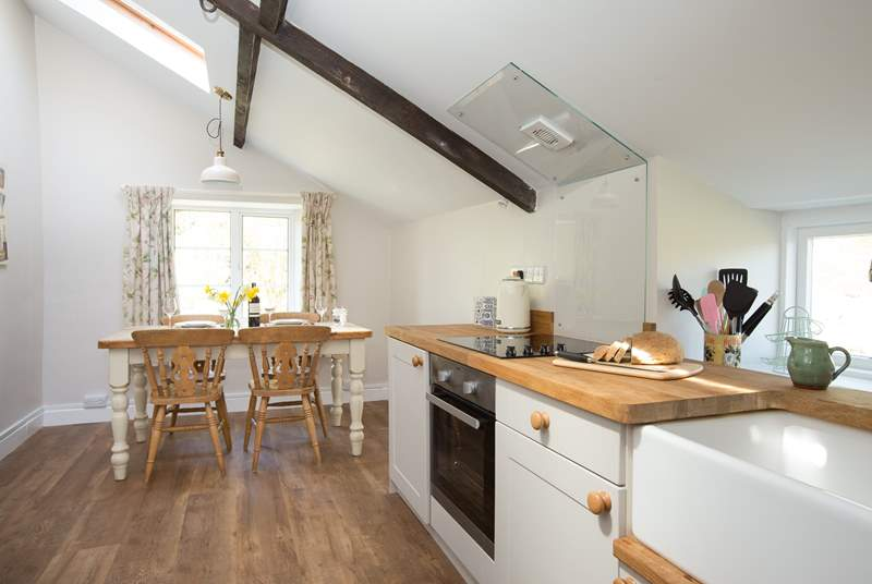 The contemporary kitchen is fully-equipped and the dining table looks out over the side garden.