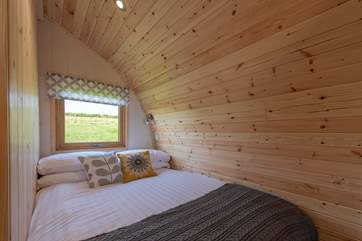 The cosy double bed is set at the rear of the pod with a window looking out to the meadow at the back.