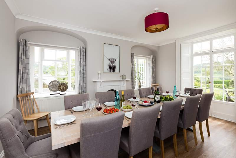 The dining room has views across the gardens and the countryside beyond. The table seats 14.
