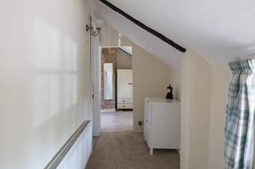 The first floor landing has a cloakroom to the left, storage space and pitched ceilings.