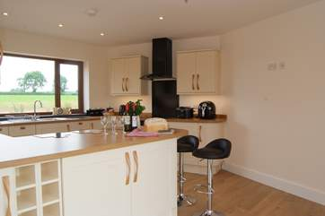 The kitchen looks out across fields at the back of the house and over the garden and lakes to the front.
