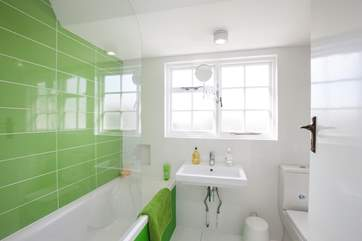 First floor bathroom with fitted shower is certainly colourful.