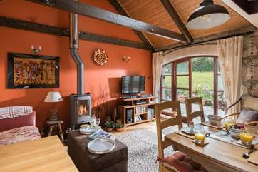 The warm and sunny open plan kitchen, dining and sitting area, with French doors leading out onto the patio (the wood-burner is ornamental).