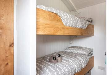 The cute bunk-beds are cleverly tucked behind a wall behind the king-size double bed.
